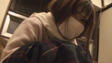 風邪でガーゼマスクを着用し厚着でストーブにあたる彼女