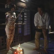 縄で縛られ磔にされた女