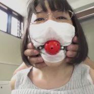 穴を空けたマスクの上から口にボールギャグを嵌め込まれる人妻
