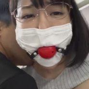 プリーツマスクの上からボールギャグを口にはめ込まれたメガネの巨乳人妻