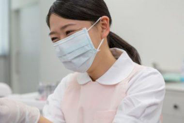 プリーツマスクを着用した笑顔がかわいい美人歯科助手