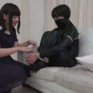 覆面とキャットスーツの姿で縛られた女強盗