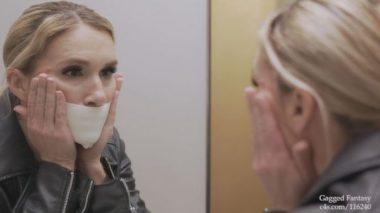 自分の口をテープで塞いでいる金髪の外国人美熟女