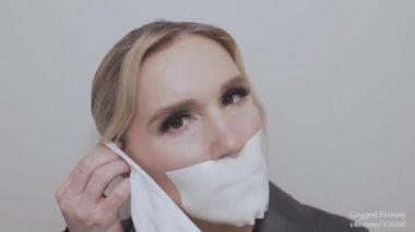 テープギャグをマスクで隠そうとする金髪美女