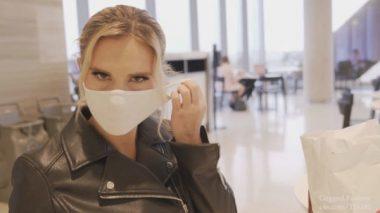 こちらを見つめながらマスクを外す外国人美熟女